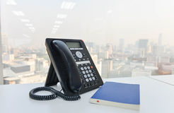 IP Phone and blue notebook on the white table Stock Photos