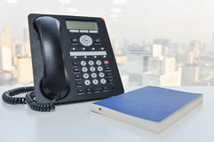 IP Phone and blue notebook on the white table Royalty Free Stock Photos