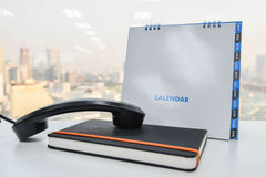 IP Phone handset on the notebook and calendar Stock Photos
