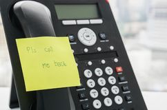 IP phone headset with calling back message on sticky note for reminder stock photos