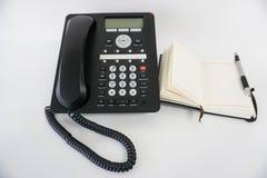 Ip-telefon och anteckningsbok Arkivbilder