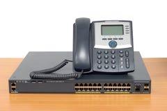 Ip-telefon och nätverkandeströmbrytare på den wood tabellen Royaltyfri Fotografi