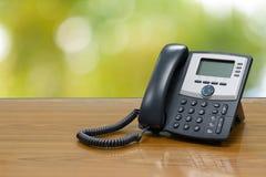 Ip-telefonapparat på den wood tabellen med suddig naturbokeh Arkivbilder