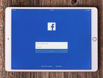 Ipad赞成与在屏幕上的社会网络Facebook,在一张木桌上 免版税库存图片