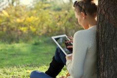 使用ipad少妇在公园 免版税库存图片