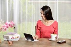 年轻俏丽的妇女看的Ipad  免版税库存照片
