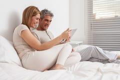 使用ipad的夫妇在床上 库存图片