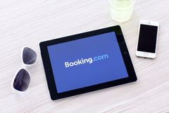 IPad with app Booking on the screen lies on a table with glasses Royalty Free Stock Image