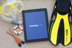IPad with app with Booking on the screen lying on the sand with Royalty Free Stock Photos