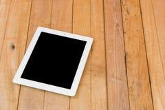 Ipad branco no fundo de madeira marrom da tabela Foto de Stock Royalty Free