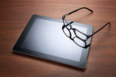 Ipad Computer Tablet and Glasses. An ipad computer tablet with glasses on a wood background Stock Image