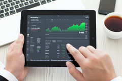 IPad con app Bloomberg en las manos de un hombre de negocios Imagen de archivo libre de regalías