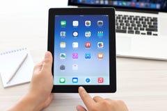 IPad con IOS 8 en manos en el fondo Macbook favorable Fotos de archivo libres de regalías