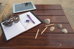 IPad, cuaderno, lápiz y pluma en la tabla de madera Imagenes de archivo