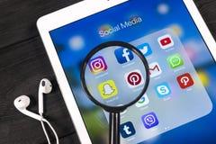 IPad de Apple con los iconos del medios facebook social, instagram, gorjeo, uso del snapchat en la pantalla debajo de una lupa Foto de archivo