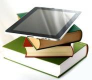 Ipad de Apple en una pila de libros imagen de archivo libre de regalías