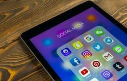 IPad de Apple favorable con los iconos del medios facebook social, instagram, gorjeo, uso del snapchat en la pantalla Medios icon Imagenes de archivo