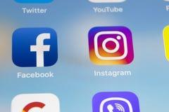 IPad de Apple favorable con los iconos del medios facebook social, instagram, gorjeo, uso del snapchat en la pantalla Tableta que Imagen de archivo