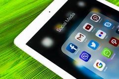 IPad de Apple favorable en la tabla de madera con los iconos del medios facebook social, instagram, gorjeo, uso del snapchat en l Foto de archivo libre de regalías