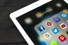 IPad de Apple favorable en la tabla de madera con los iconos del medios facebook social, instagram, gorjeo, uso del snapchat en l Imágenes de archivo libres de regalías