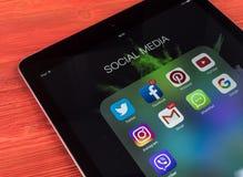 IPad de Apple favorable en la tabla de madera con los iconos del medios facebook social, instagram, gorjeo, uso del snapchat en l Fotos de archivo