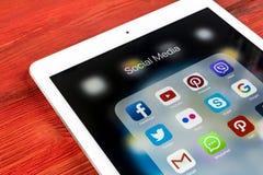 IPad de Apple favorable en la tabla de madera con los iconos del medios facebook social, instagram, gorjeo, uso del snapchat en l Imagen de archivo libre de regalías
