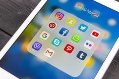 IPad de Apple favorable en la tabla de madera con los iconos del medios facebook social, instagram, gorjeo, uso del snapchat en l Fotos de archivo libres de regalías