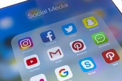 IPad de Apple favorable en la tabla de madera con los iconos del medios facebook social, instagram, gorjeo, uso del snapchat en l Imagenes de archivo