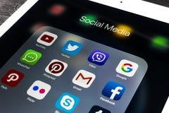 IPad de Apple favorable en la tabla de madera negra con los iconos del medios facebook social, instagram, gorjeo, uso del snapcha Foto de archivo