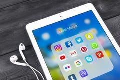 IPad de Apple favorable en la tabla de madera negra con los iconos del medios facebook social, instagram, gorjeo, uso del snapcha Fotos de archivo