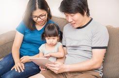 IPad de observación del papá y de la mamá con su niña Foto de archivo libre de regalías