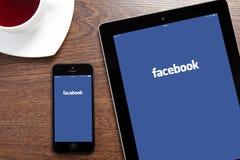 IPad e IPhone con Facebook su uno schermo Fotografia Stock Libera da Diritti