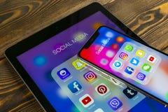 IPad e iPhone X de Apple con los iconos del medios facebook social, instagram, gorjeo, uso del snapchat en la pantalla Medios ico Fotos de archivo libres de regalías