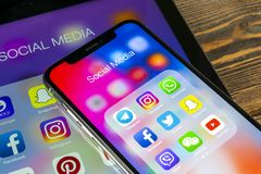 IPad e iPhone X de Apple con los iconos del medios facebook social, instagram, gorjeo, uso del snapchat en la pantalla Medios ico Fotografía de archivo libre de regalías