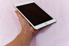 Ipad in hand. Apple new ipad mini4 White gold ipad Stock Photo