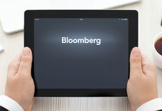 IPad met app Bloomberg in de handen van een zakenman Stock Fotografie