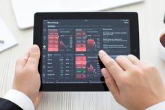 IPad met app Bloomberg in de handen van een zakenman Stock Afbeelding