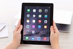 IPad met IOS 8 in handen op achtergrond Macbook Royalty-vrije Stock Foto's