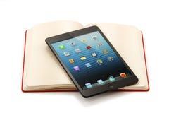 Ipad mini op open boek - het knippen weg Stock Afbeelding