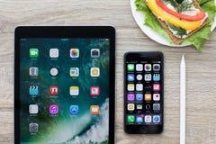 IPad Pro und iPhone mit Hauptschirm in der Tabelle Stockbilder