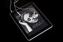 Ipad que joga o álbum 21 de Adele Foto de Stock