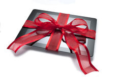Ipad Tablet Christmas Present Gift. An ipad tablet Christmas present with a red bow on a white background stock photos
