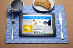 Ipad Tablet Online Breakfast Newspaper. An ipad tablet on the breakfast table with the world news, coffee and croissant Royalty Free Stock Photos