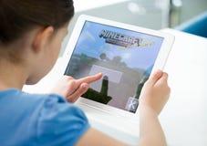 演奏在苹果计算机iPad空气的小女孩Minecraft 库存照片