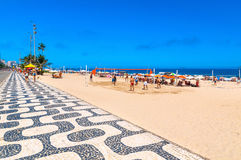 Ipanema beach with mosaic of sidewalk and people playing volleyball in Rio de Janeiro Royalty Free Stock Photos