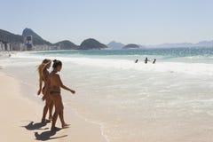 IPANEMA BEACH, RIO DE JANEIRO, BRAZIL - NOVEMBER 2009: two girls. Two girls in bikinis walking into the ocean at Ipanema Beach Royalty Free Stock Image
