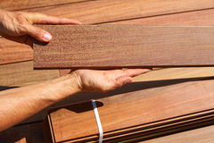 Ipe deck installation carpenter hands holding wood Stock Photo
