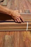 Ipe deck installation carpenter hands holding wood Stock Image