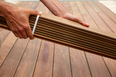 Ipe deck installation carpenter hands holding wood Stock Images