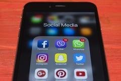 iphone与社会媒介象的7个加号在屏幕上的在红色木书桌上 智能手机生活方式智能手机 开始社会媒介 免版税库存图片